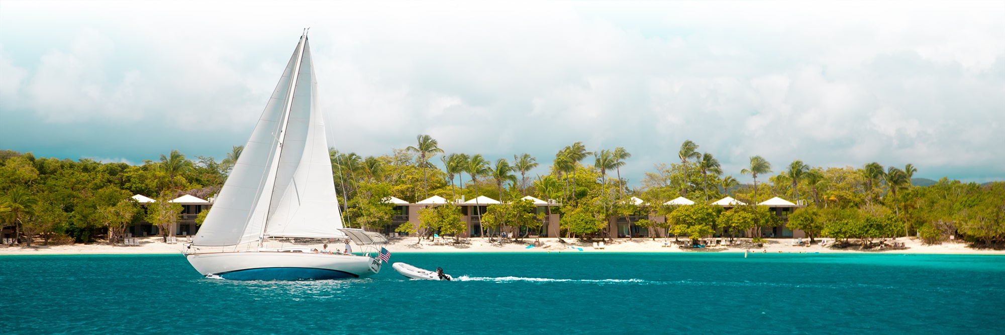 panoramic view of a sloop under full sails sailing close by Caneel Bay, St.John, US Virgin Islands