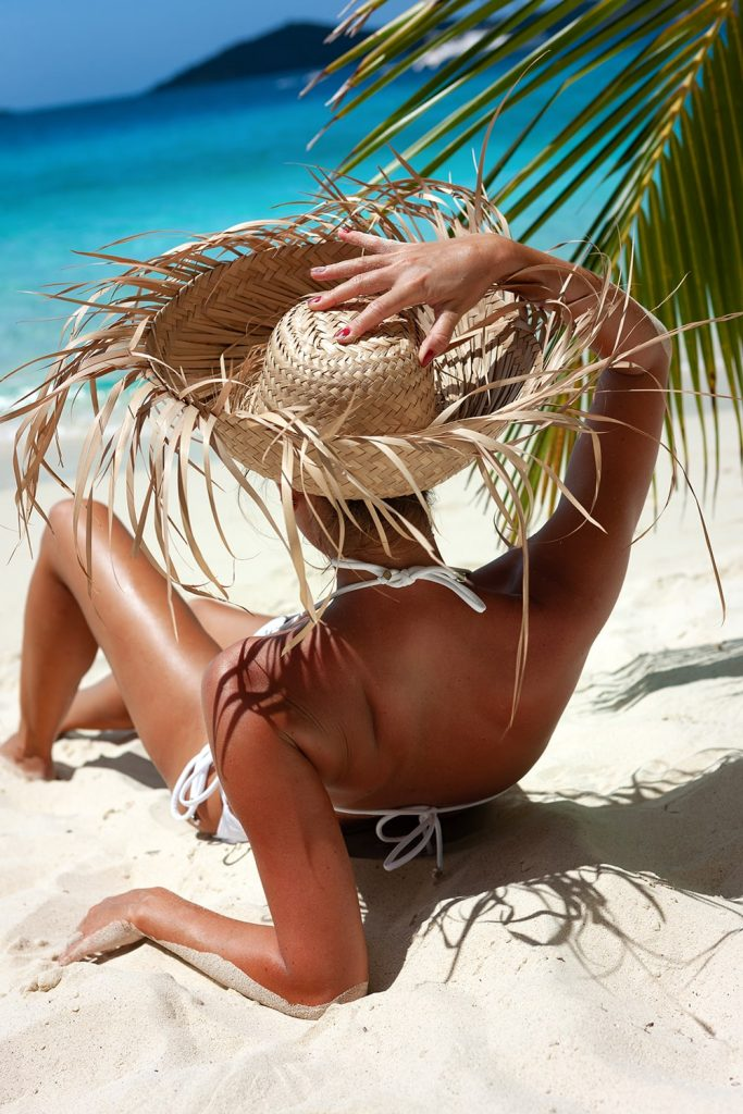 Bikini straw hat woman relaxing under a palm tree on a perfect beach in the Carribean